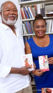 Hon. Louis Mussington (L), presents books published in St. Martin to Marie Michele Raymond, Head of the legal deposit of the National Library of Haiti. While in Port-au-Prince Mussington attended CARIFESTA XII activities, August 21 – 30, 2015. (© CLF photo)