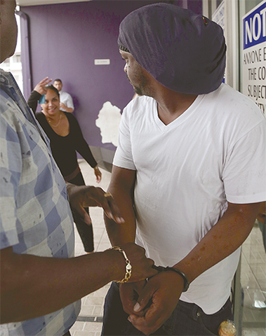 An unidentified woman heckles Ricardo Jerome outside the Arima Magistrates' Court yesterday. PHOTO: MARCUS GONZALES