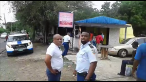 Police officer Gilles Ellis is seen talking to chief Commissioner of police Carl John